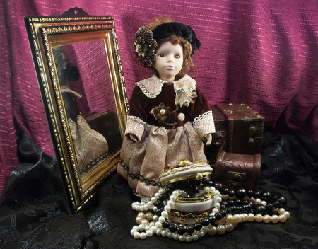 fashion doll: Retro fashioned porcelain doll with jewelry box. Composition of a retro fashioned porcelain doll in dress with border lace, jewelry  beret standing with antique mirror  chests.