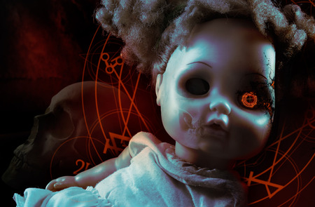 children face: Possessed demonic doll. Possessed demonic horror doll with red pentacles, glowing eye  human skull on background. Stock Photo