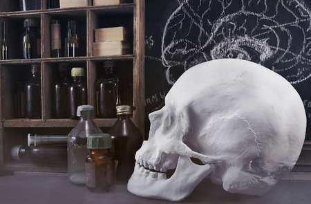 apothecary: Old pharmacy medicine alchemy table with bottles on shelves, board with brain illustration, skull and dirty syringe. Stock Photo