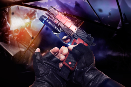 Hand in black gloves holding a red neon recharging handgun. First person view hand in black leather gloves holding a futuristic fantasy neon recharging handgun with clip and neon red, blue indicators. Stock Photo