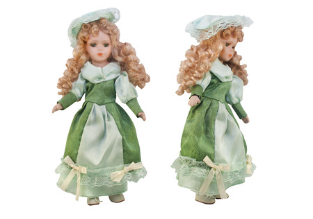 Isolated photo of old-fashioned doll in green dress with hat and curly hair on white background. Stockfoto