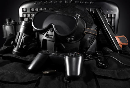 Tactical helmet, gloves, gun, binoculars laying on a jacket with gamepad & keyboard on background.
