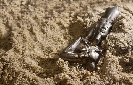 Old ancient metal pharaoh statuette laying in sand.