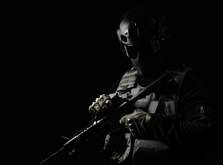 Black and white photo of equipped swat soldier standing with rifle on black background.