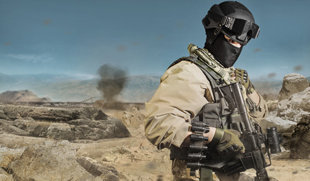 Photo of a fully equipped military soldier standing with rifle, ammo on desert battlefield background.