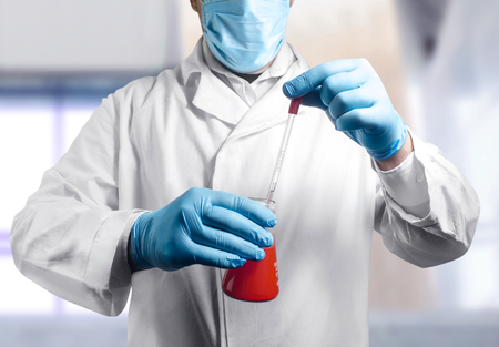 Photo of a lab assistant in outfit holding a flask and pipette. Stock Photo