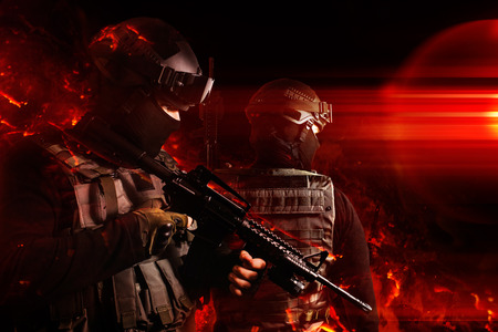 Photo of a swat soldiers posing with automatic rifle in flame effects. Banco de Imagens