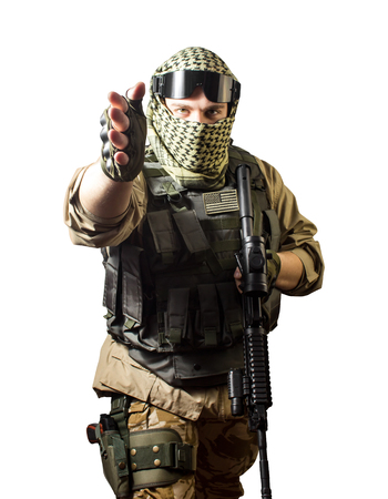 Isolated photo of a fully equipped military soldier standing with rifle and tactical glasses showing military hand sign towards camera. Banque d'images