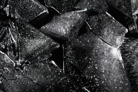 Photo texture of a black and white ice laying on dark background. Stock Photo