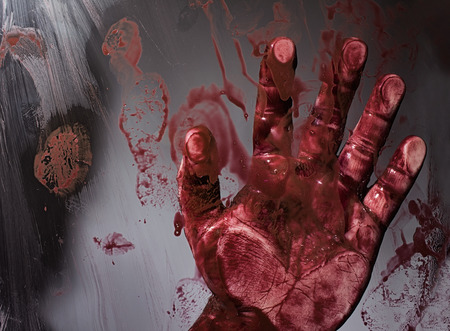 Scary horror bloody victims hand touching transparent splattered glass depicting murder scene. Stock Photo