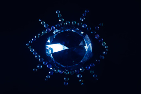 Photo composition of a diamond and small stones in a shape of an eye laying on a black surface.