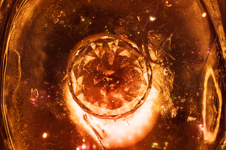 Photo of a diamond upped view with fire effects laying on ice background with sparkles.