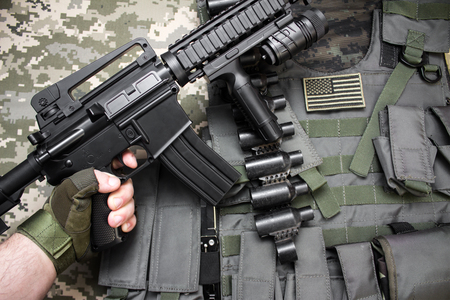 First person view hand in tactical gloves holding a rifle on military camouflage and armor bulletproof vest background texture.