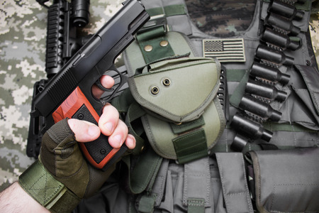 First person view hand in tactical gloves holding a gun on camouflage background with bulletproof vest and cartridge belt. Stock Photo