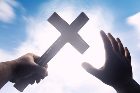 First person view photo of a male hands holding a cross on a bright light shine with blue skies background.