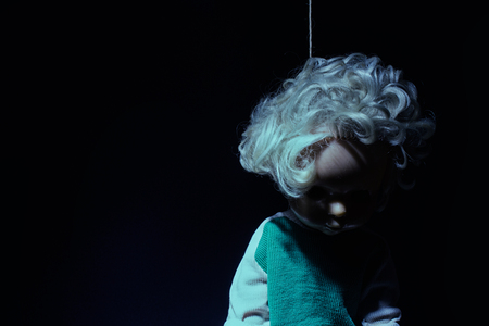 Dark themed hanged scary blue toned suicidal doll on black background. Stock Photo
