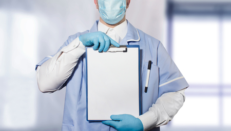 Photo of a doctor in full outfit and rubber gloves holding a tablet with empty papers in both hands. Stock Photo