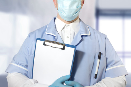 Photo of a lab assistant in full outfit and rubber gloves holding a tablet with empty papers in one hand.