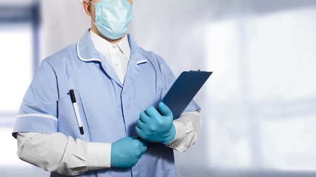 Photo of a lab assistant in full outfit and rubber gloves holding a tablet with empty papers in both hands. Stock Photo