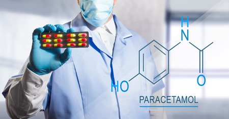 Photo of a lab assistant holding a pill blister with paracetamol with chemical formula near to him. Stock Photo
