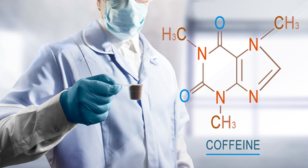Photo of a lab assistant holding a coffee in measuring cup with chemical formula near to him.