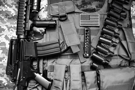 Upper view photo of a military tactacal bulletproof vest, cartrige belt and rifle laying on camouflage cloth background.