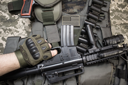 Upper view photo of hand in tactical gloves holding a rifle on military tactacal bulletproof vest, cartrige belt laying on camouflage cloth background.