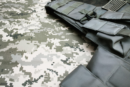 Angle view photo of a military bulletproof vest laying on a camouflage cloth background.