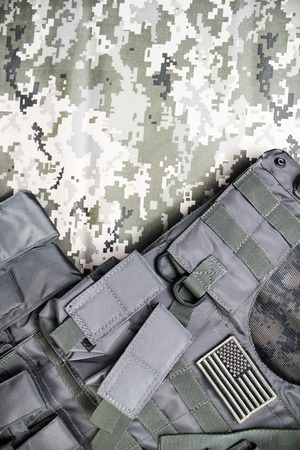 Upper view photo of a military bulletproof vest laying on a camouflage cloth background. Stock Photo