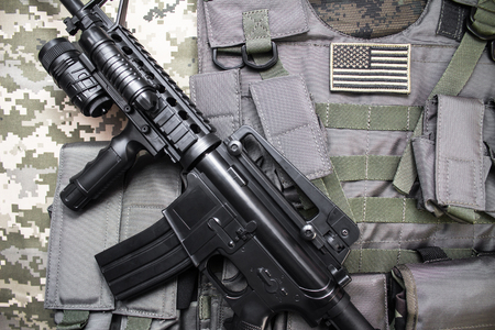 Upper view photo of a military bulletproof vest with american flag badge and rifle laying on a camouflage cloth background.