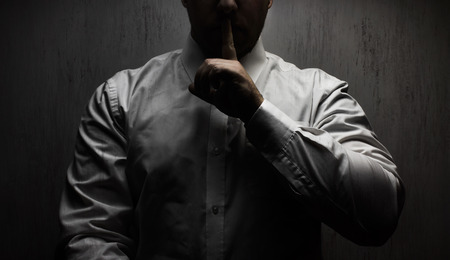 Photo of a scary horror man in white shirt standing under upper light on black background showing silence hand sign.