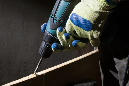 Closeup photo of a worker in outfit with blue gloves using drill with wooden board on black background with upper light.