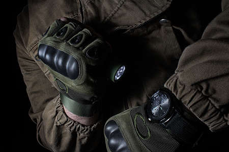 Photo of a male person in brown tactical outfit jacket and gloves using green tactical led flashlight and military watch. Stock Photo