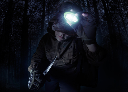 Profile view photo of a male person in brown tactical outfit jacket, gloves and knife turning on head flashlight on night woods background.
