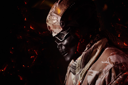 Military skeleton soldier in camouflage outfit profile view with fire ashes flying standing on black background.