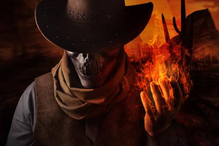Photo d'un cow-boy à tête de crâne démoniaque en chapeau tenant un sort de feu avec son bras sur un fond de désert au coucher du soleil.