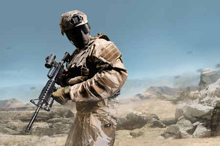 Profile view military fully equipped soldier in outfit posing with rifle on  desert background. Stok Fotoğraf