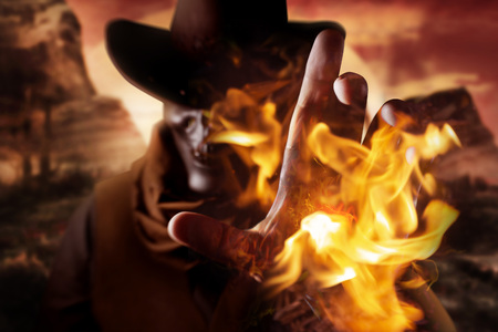 Photo of a demonic skull head cowboy in hat casting fire spell with his arm on a sunset desert background.