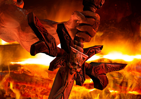 Illustrazione di una mano di demone con unghie affilate che tiene una spada incisa con teschio vista ravvicinata sullo sfondo del fuoco.