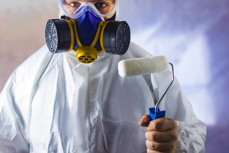 Worker in protective suit and respirator holding a paint roller in his hand close up view on abstract blurred background.