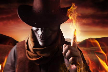 Photo of a demonic skull head cowboy in hat casting fire spell with his arm and finger on a sunset desert background.