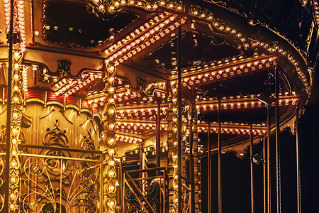 Photo of a lightened up golden carousel with red and yellow light bulds closeup view. Stok Fotoğraf