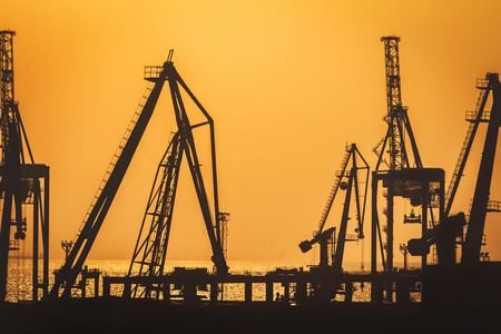 Silhouettes of sea ship cranes on a orange toned warm sunset background. Stok Fotoğraf