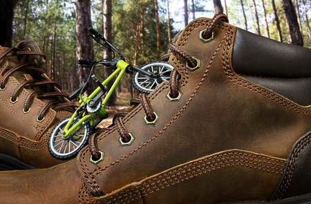 Concept of traveling boots with toy bike standing on woods background. Standard-Bild