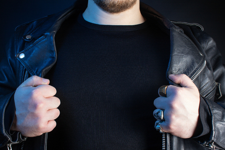 Photo of a biker in black leather jacket with skull rings torso copyspace on black background.