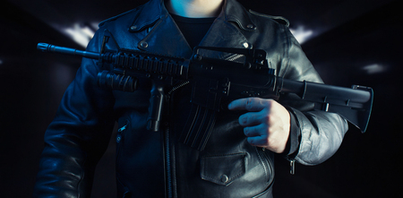 Photo of a biker in black leather jacket with skull rings holding rifle on black background torso view.