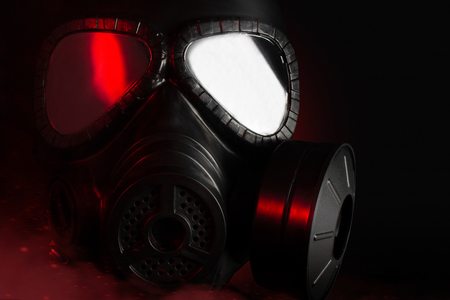 Photo of a black military gas mask with red highlights laying on black background.