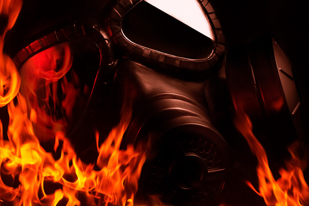 Photo of a black burning military gas mask laying in flames on black background. Stok Fotoğraf