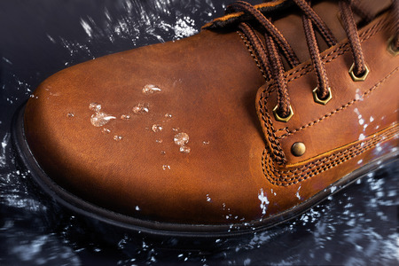 Concept photo of a worker and travel brown leather boot stepping into water with splash on surface.