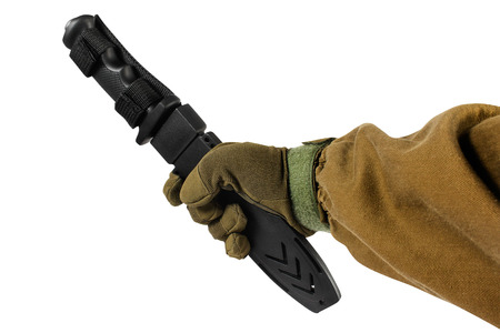 Isolated first person view photo of a hand in brown tactical gloves and jacket holding black hunting and military knife in sheath on white background. Stock fotó
